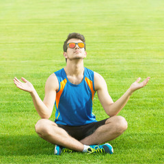 Athletic man sitting on the grass and relaxing