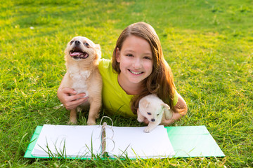 kid girl and puppy dog at homework lying in lawn
