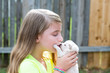Blond kid girl with puppy pet chihuahua playing