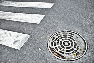 Manhole cover on asphalt road with pedestrian crossing marking