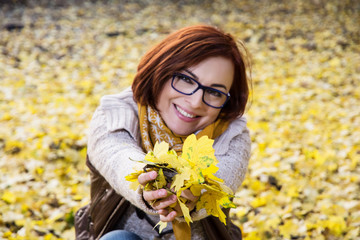 Smiling redhead woman with yellow autumn leaves