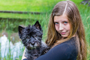 Girl carrying black dog on arm in park.