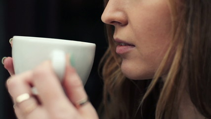 Closeup of beautiful woman drinking coffee in cafe
