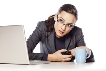 Business woman secretly texting on the phone at her desk