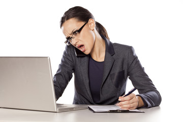Angry woman working on a laptop, talking on the phone and write