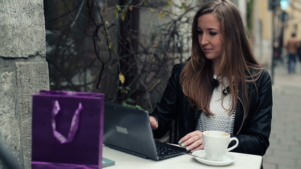 Young beautiful woman with laptop having coffee break in cafe