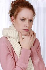 Frau mit Schal und Halsschmerzen