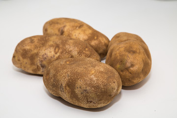 Four Potatoes on a White Counter