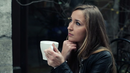 Young beautiful pensive woman sitting alone in cafe