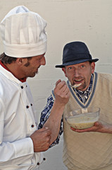 Koch füttert Bauer