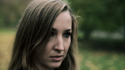 Portrait of sad young beautiful woman in the park