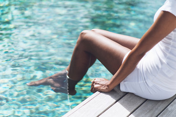 Woman Resting at Poolside with Feet on Water