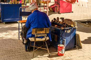 Alter Schuhmacher sitzt am Strassenrand in Tunis