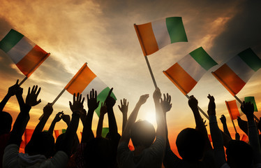 Silhouettes of People Holding Flag of Ireland