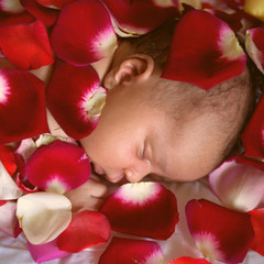 Black baby sleeping in rose petals