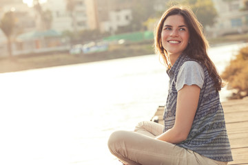 beautiful smiling girl with sitting and resting on a pier