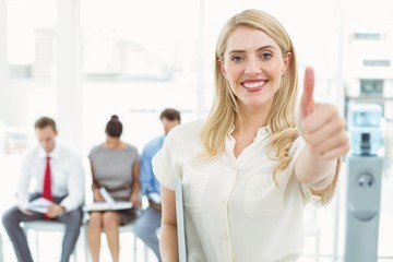 Businesswoman gesturing thumbs up