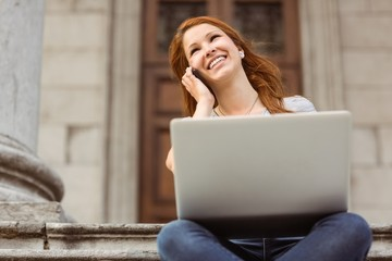 Smiling girl calling with her mobile phone and using laptop