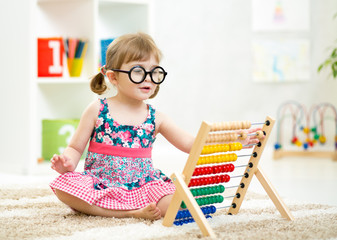 child kid weared glasses playing with abacus toy