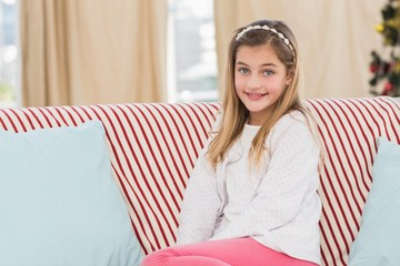 Cute little girl sitting on couch