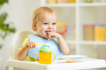 happy baby kid boy eating itself with spoon