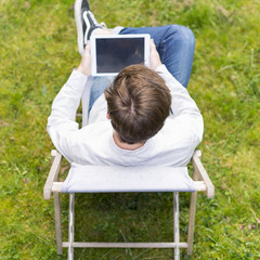Bird view on unrecognizable person with digital tablet sitting o