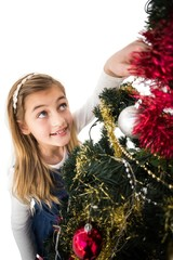 Festive little girl decorating christmas tree