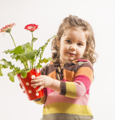 Portrait of a beautiful little girl holding vase with flowers