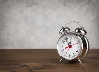 Alarm clock on table over vintage background
