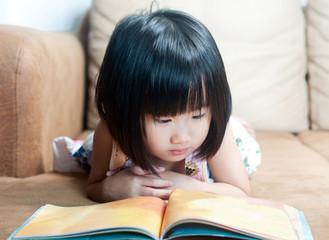 Asian little girl reading her book