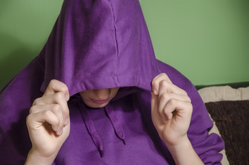 Scared boy covered his face with a hood domestic violence