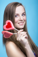 beautiful model with lollipops in the shape of a heart