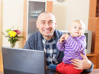 father and baby daughter at  laptop