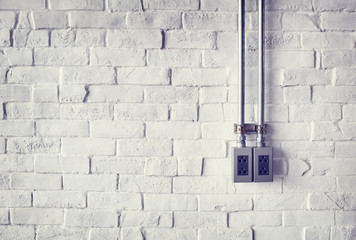 Electrical Socket on a White Painted Brick Wall