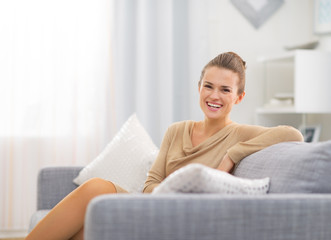 Portrait of smiling young housewife in living room