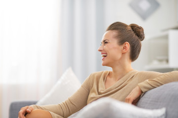 Smiling young housewife in living room