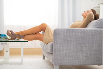 Relaxed young housewife laying on divan in living room