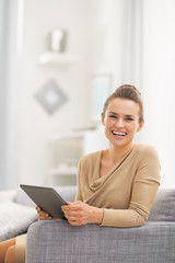 Portrait of happy young woman with tablet pc in living room
