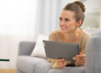 Thoughtful young woman laying on couch and using tablet pc