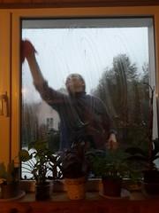Взрослая женщина моет окно в своем доме