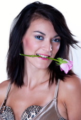 Girl bitten pink rose with her teeth