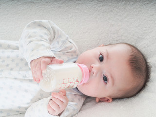 Baby boy  drinking milk from the bottle at home