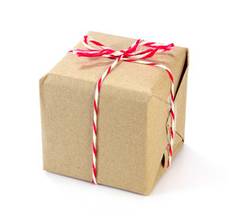 brown paper parcel tied with red and white string on white backg