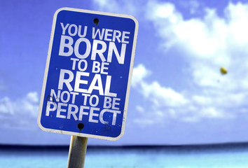 You Were Born To Be Real Not To Be Perfect sign with a beach