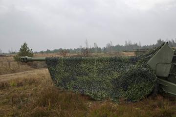 artillery gun under camouflage net