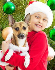 charming kid in Christmas clothes holding his dog