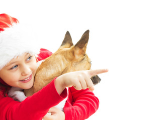 little girl in Christmas clothes pointing her finger on a white