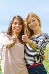 Zwei junge Frauen mit Daumen nach oben