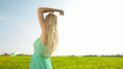 Beautiful blonde girl in dress dancing in the green field