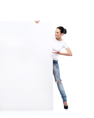 Teenage girl in denim jeans holding a blank banner on white